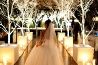 05 lit white trees are a great idea for a winter wonderland wedding aisle
