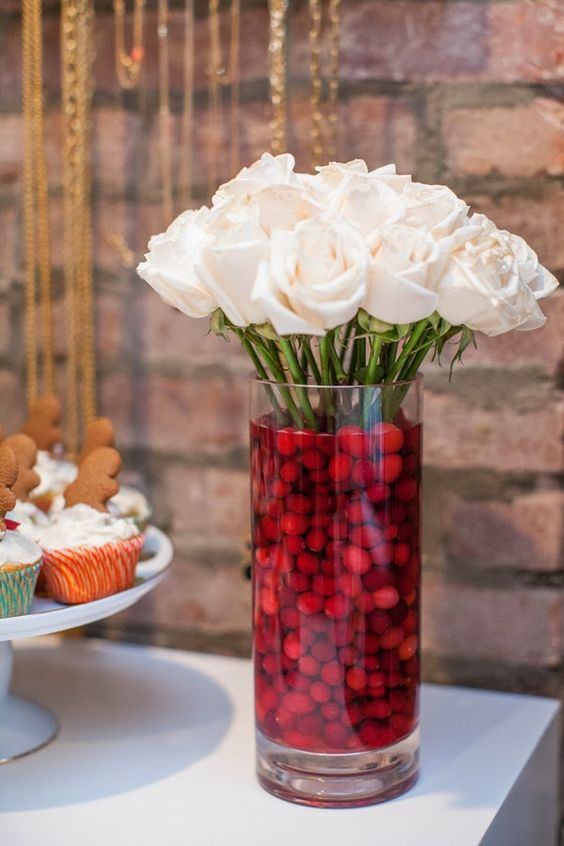 white rose arrangement and a vase filled with cranberries