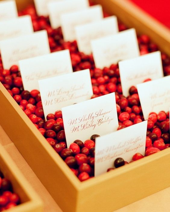 golden trays filled with cranberries to hold the escort cards