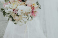 07 Lush, pastel bridal bouquet filled with peonies and ranunculus