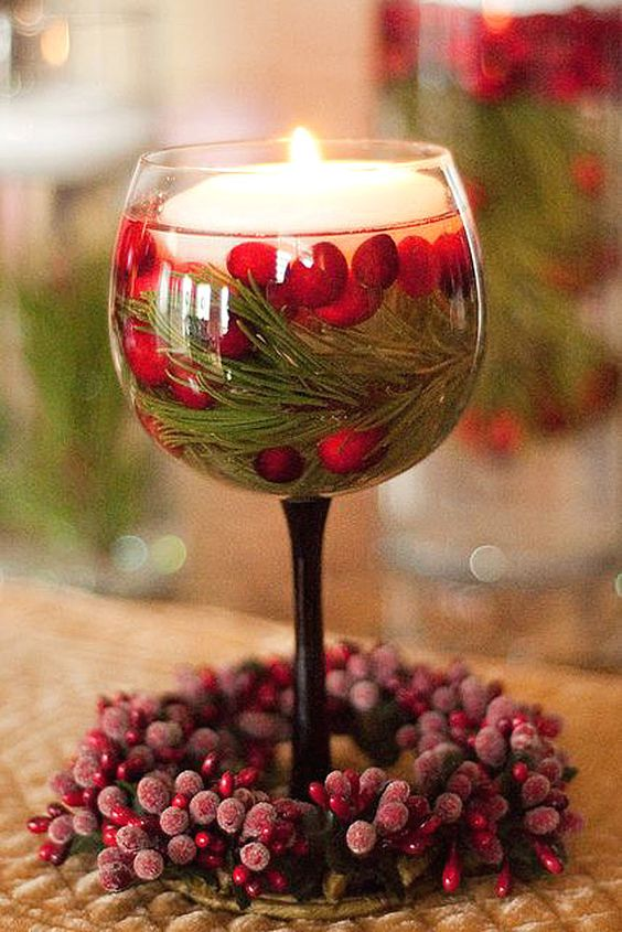 glass with a floating candle, fir branches and cranberries