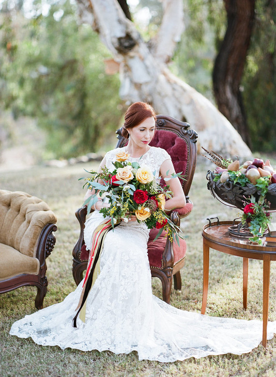 the bride has a lush bouquet in fall tones with bold ribbons