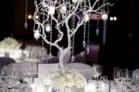 09 all-white table with a white tree made of branches and decorated with candle holders and crystals
