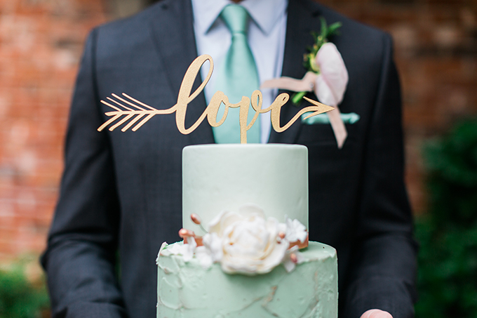 The groom was wearing a dark grey suit with a mint tie to match the color scheme