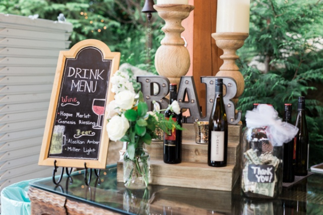 Rustic bar with a light sign and a chalkboard drink menu