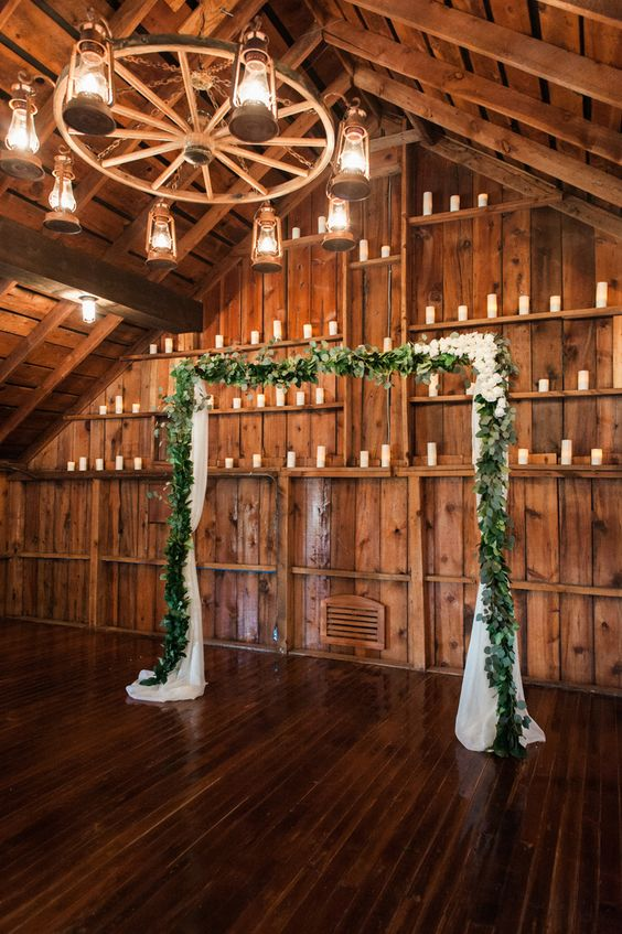 indoor wedding arches. simple eucalyptus garland wedding arch for a barn and candles around an ambience indoor arches