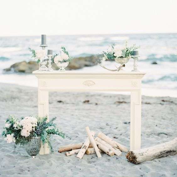 faux fireplace with firewood, blue candles and white flowers
