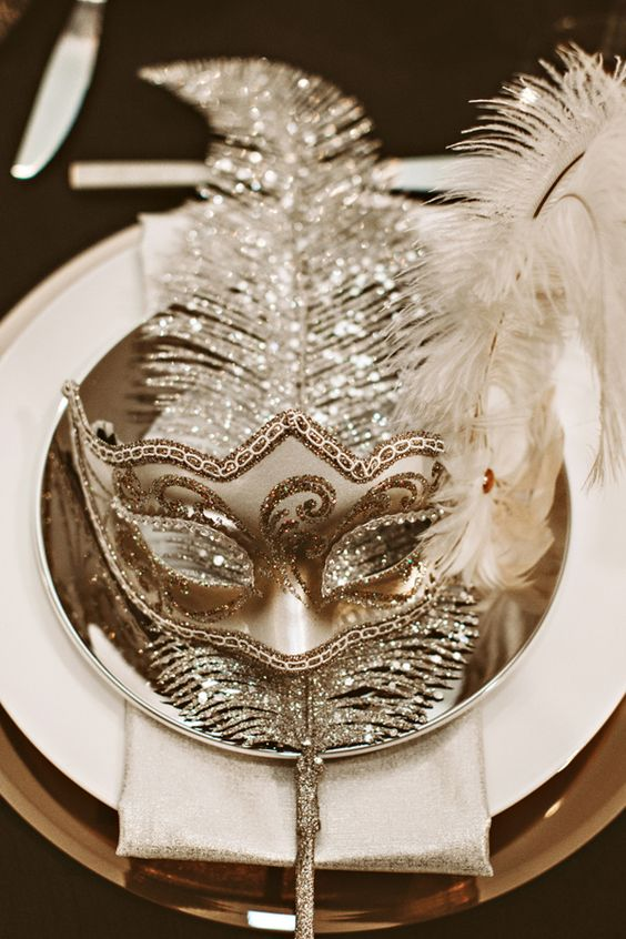sparkling masks with feathers placed at each table