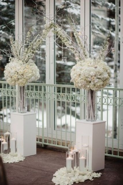 white floral arch with floating candles and petals for winter wonderland weddings