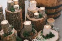 14 use wood logs decorated with moss as candle stands