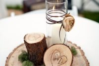 16 a simple centerpiece of a candle and wood placed on a wood slice