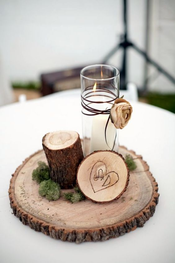 a simple centerpiece of a candle and wood placed on a wood slice