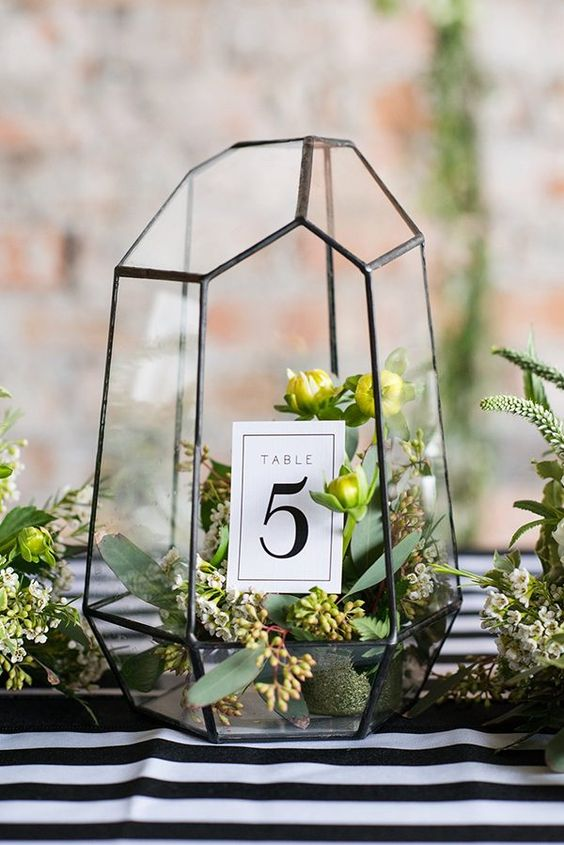 black geo terrarium with fresh greenery and table numbers inside