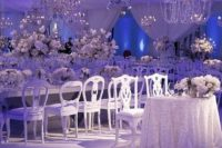 20 winter wonderland scene with crystal chandeliers and beautiful white blooms that filled this custom, sheer-draped tent