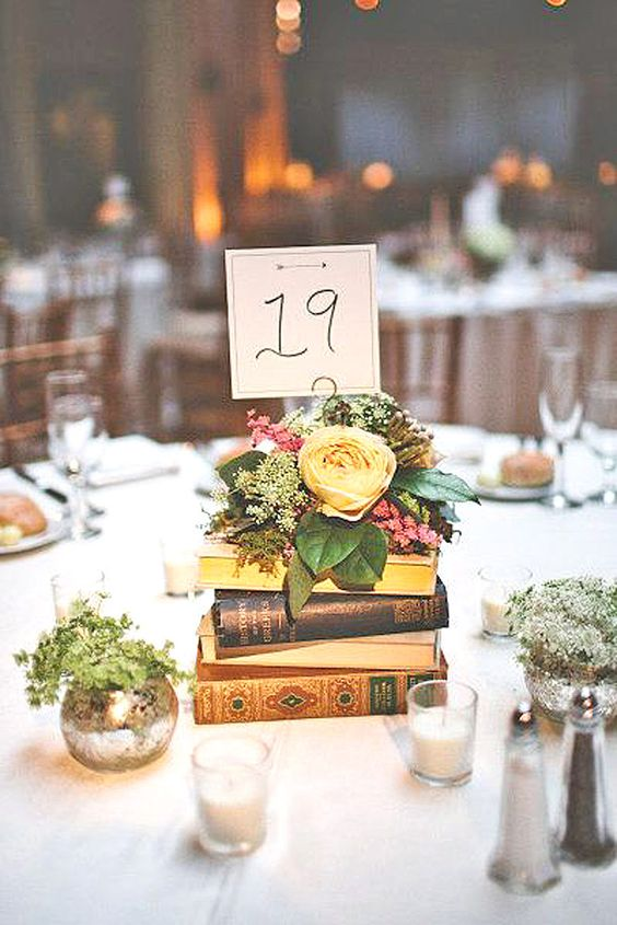 stacked books topped with flowers and a table number