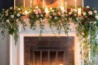 24 a non-working fireplace decorated with candles, greenery and blush and red roses