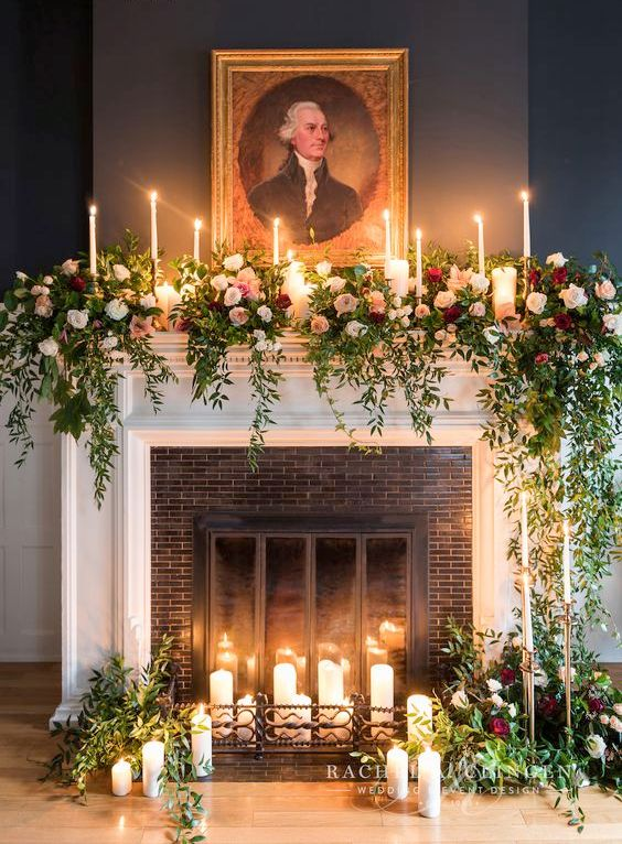 a non-working fireplace decorated with candles, greenery and blush and red roses