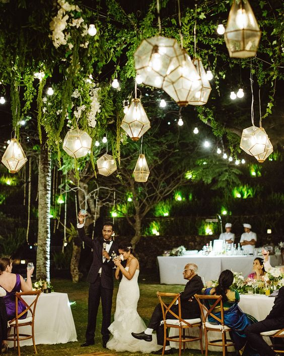 geo lanterns glowing in greenery for an outdoor wedding