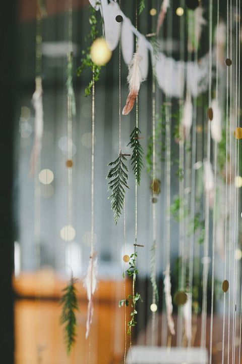 fir branch garlands with feathers and gold dots will give your wedding a boho feel