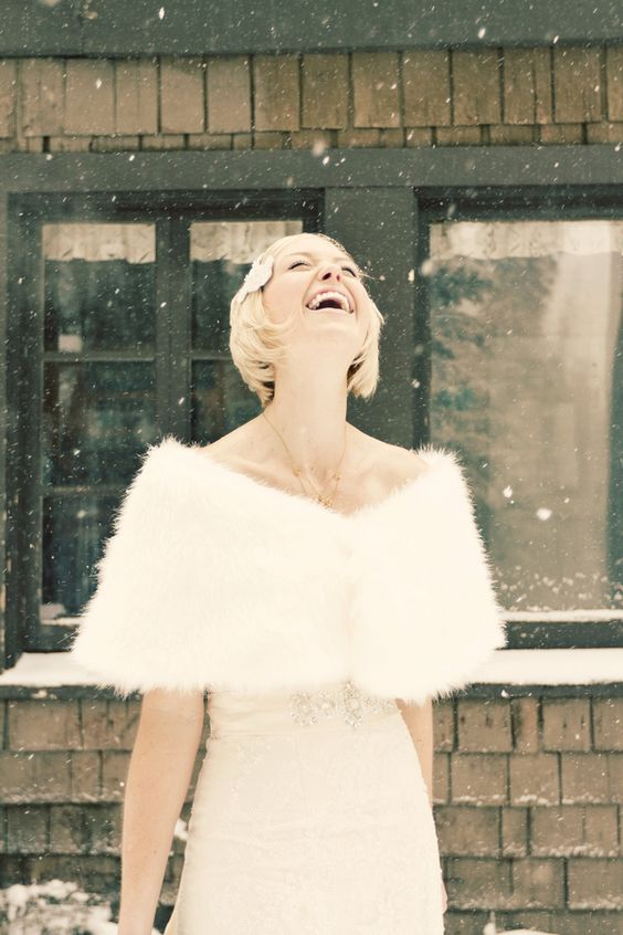 bride in the snow wearing a winter wedding faux fur coverup