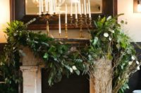 26 fireplace decorated with lush greenery, birch logs and candle holders