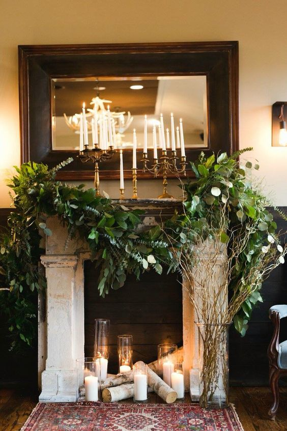 fireplace decorated with lush greenery, birch logs and candle holders