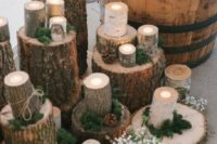 27 place moss and pinecones on wood logs and top them with candles