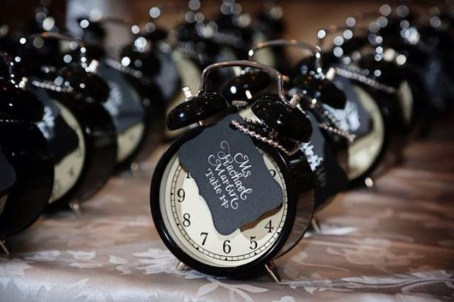 seating cards attached to cool little clocks as favors