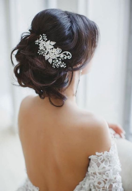 a messy updo with a rhinestone and bead hairpiece