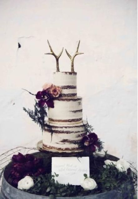wedding cake decorated with dark moody flowers and antlers instead of toppers