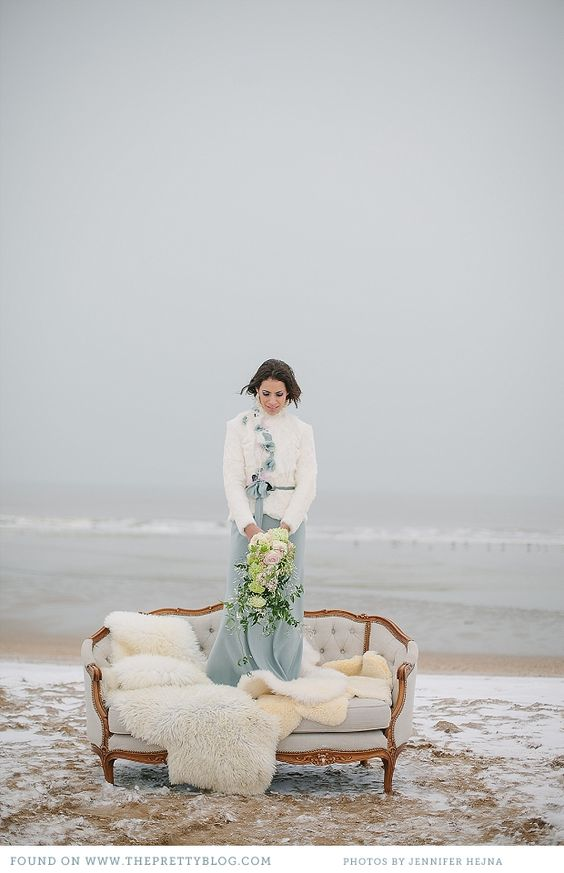 winter coastal bride in a blue grey dress and a white ribbon jacket