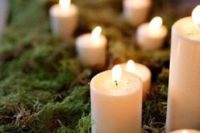 35 pillar candles dressed up with moss, which screams forest
