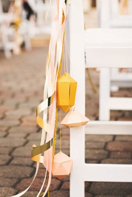 give your ceremony's aisle markers a contemporary touch by including geometric shapes with gold and pink ribbon
