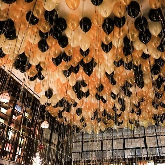 ceiling decorated with cream, gold and black balloons