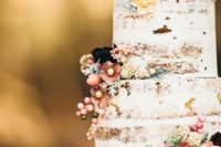 42 lightly frosted wedding cake with berries and flowers