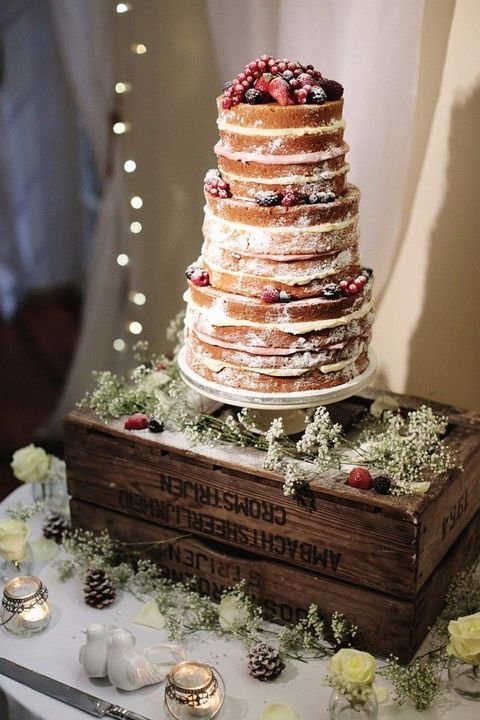 naked wedding cake topped with fresh berries and fruit