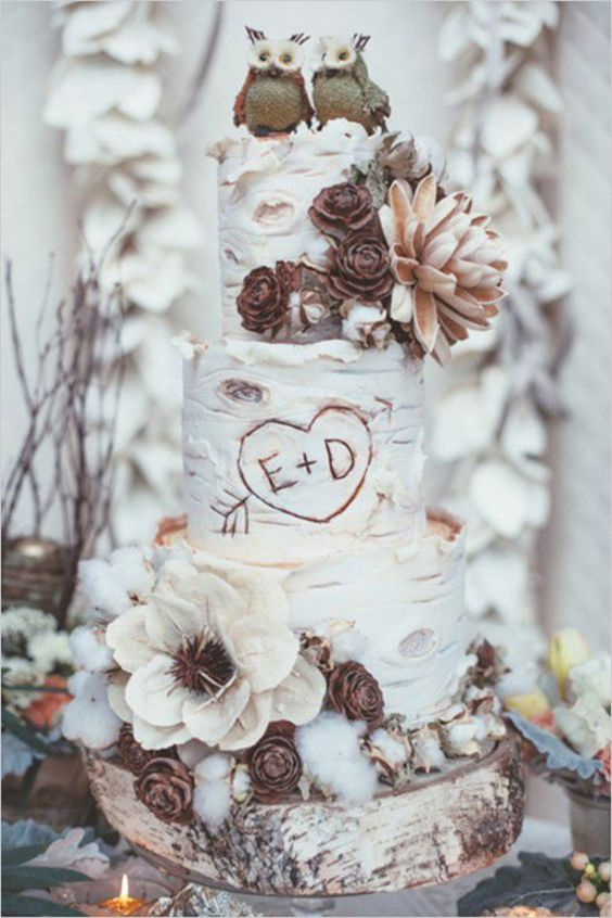wedding cake looking like a birch one decorated with cotton, pinecones and fabric owl toppers