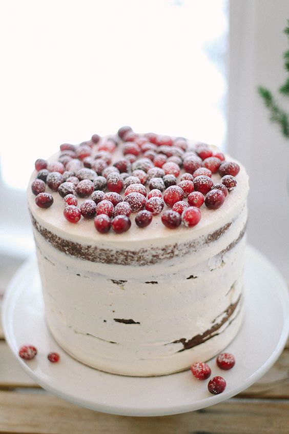 frosted wedding cake topped with cranberries and sugar powder