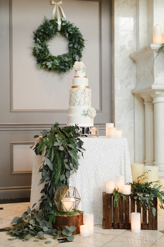 hang a winter wedding wreath as a backdrop for your dessert table and add a echoing garland to the table itself