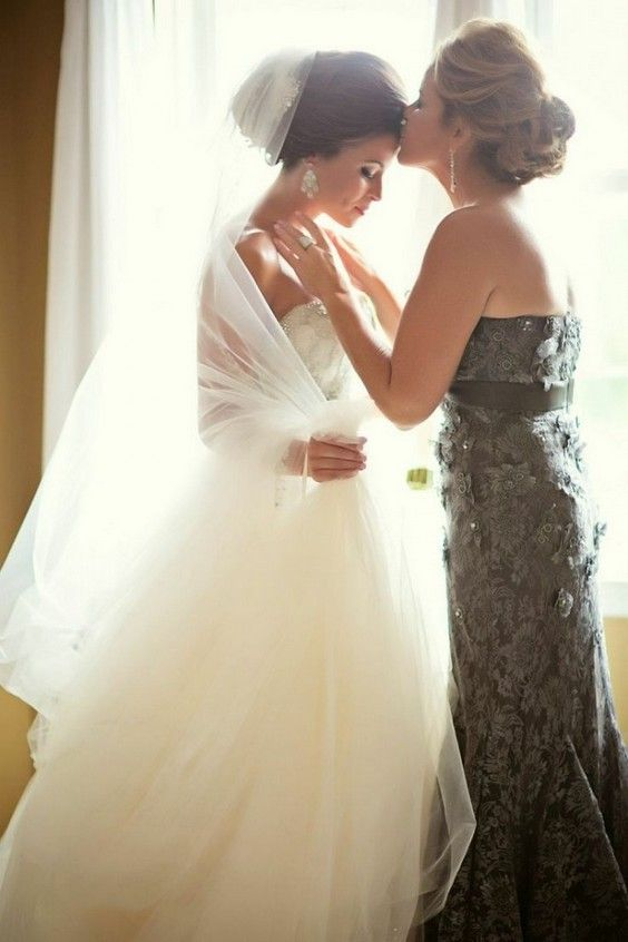 mother kissing her beautiful daughter before going down the aisle
