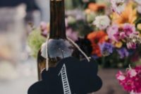 02 wine bottles with chalkboard table numbers tied with twine