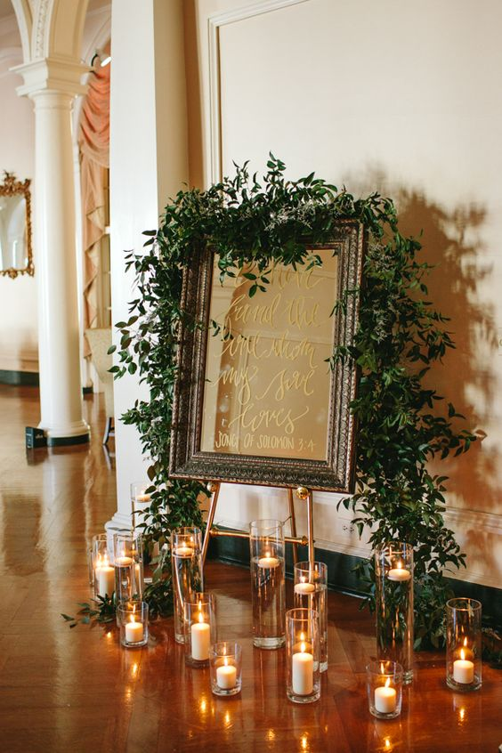 framed mirror calligraphy wedding signage decorated with greenery and pillar candles