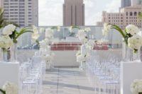 03 modern rooftop wedding aisle with white flowers and lucite chairs