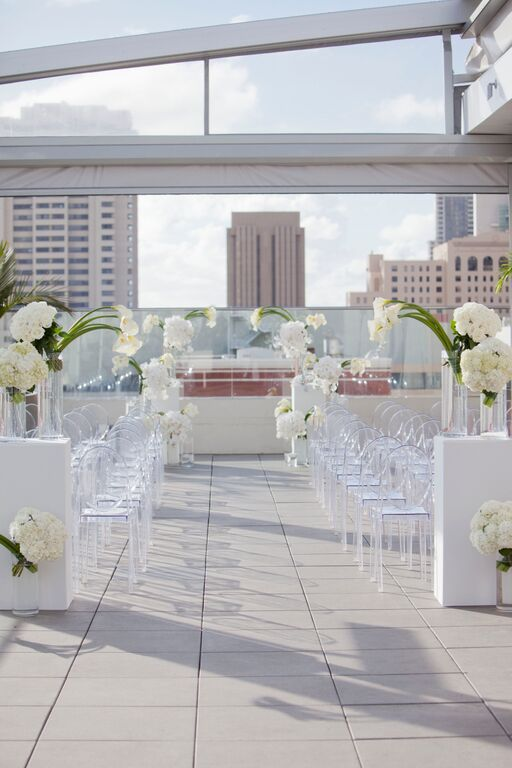 modern rooftop wedding aisle with white flowers and lucite chairs