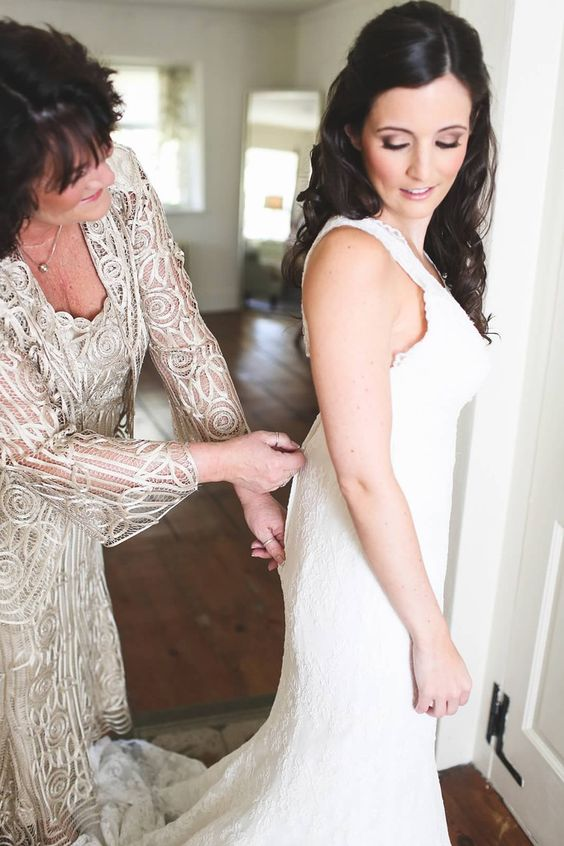 mom helping her daughter to put on the dress