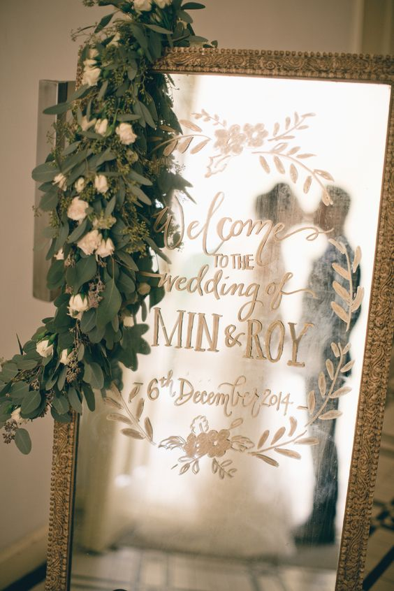 large vintage mirror with handwriting decorated with a lush greenery and flower garland