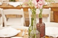06 clear, green and brown wine bottle vases tied with yard and a wood slice with a number