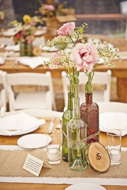 clear, green and brown wine bottle vases tied with yard and a wood slice with a number