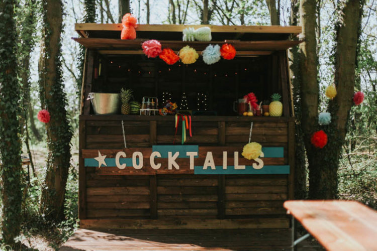 A cute rustic cocktail bar was decorated with colorful pompoms and paper, there was a marquee light