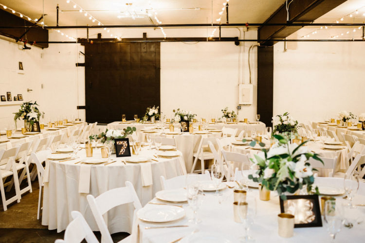 The venue was decorated simple, in black and white, with greenery and flower centerpieces